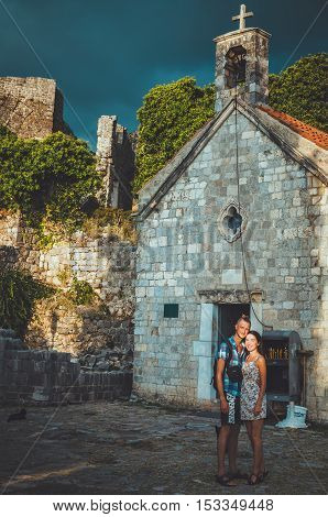 STARI BAR, MONTENEGRO - September, 2016: Happy loving young couple posing near tiny church in the ancient fortress of Old Bar. Romantic summer holidays travel concept in Europe. Man and woman embracing