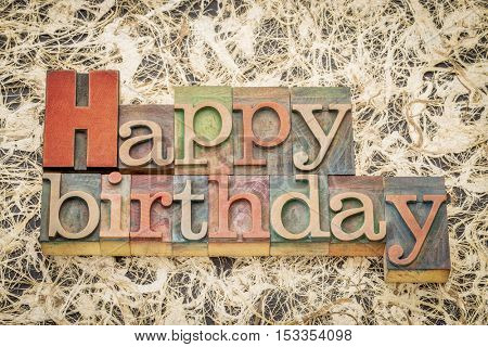 Happy Birthday greeting card - word abstract in letterpress wood type against amate paper