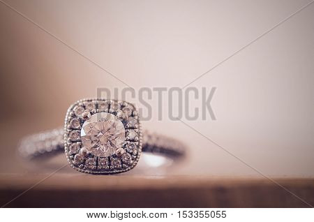 Closeup of diamond engagement ring on soft background.