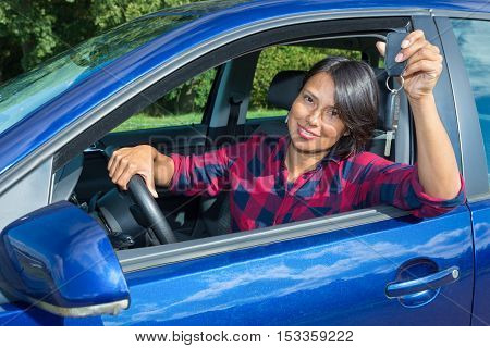 European woman behind the car wheel showing car key