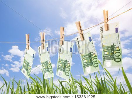 100 Euro Banknotes Hanging On Clothesline On Grassland Background.