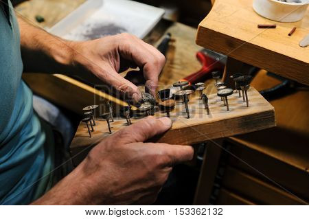 Craft jewelery making. Jeweller selects a tool to polish the ring.