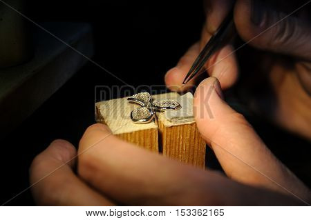 Craft jewelery making. Jeweller fixes sapphires on the ring.