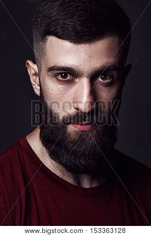 closeup portrait of a bearded man on dark background