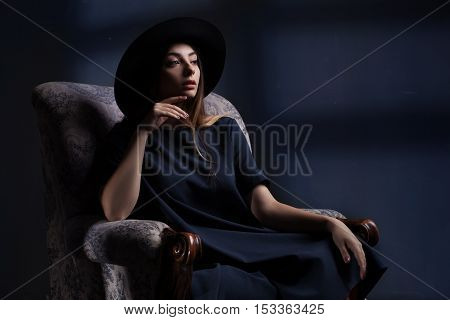 studio portrait of a amazing beautiful smiling woman in black dress and a gat over dark blue background