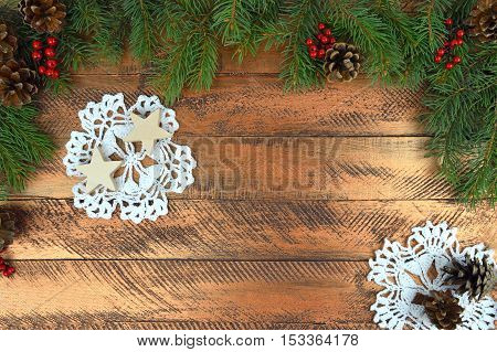 Christmas background in rustic style. Christmas tree pine cones berries handmade stars Grandma's crocheted napkinson the old wooden background. Top view.Nostalgia. Communication of generations.
