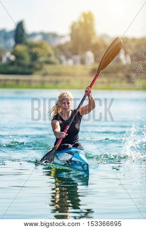 Female athelete training kayaking on lake, toned image