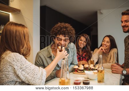 Young girl feeding her boyfriend with burgers.
