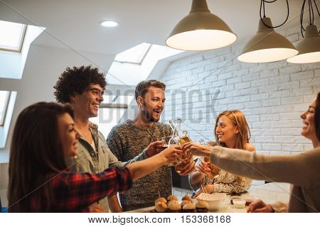 Friends enjoying beer and burgers at home party.
