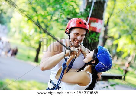 enamored guy and the girl in special equipment on the rope way. Boy and girl smiling extremists passing obstacles in the amusement park