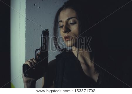 brunette girl with gun in a garage in attitude shoot, dressed in bulletproof vest
