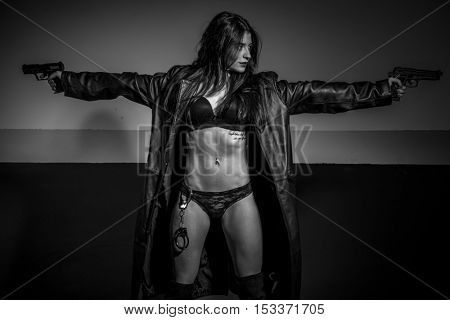 Military brunette girl with long leather coat and lingerie with machine gun and pistol posing dangerous in a garage