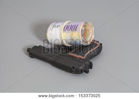 Swiss thousand francs in a roll and gun gray background