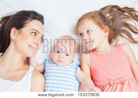 Happy family mother with her children looking at camera at white background. Newborn and child. Mothercare is most important in children life. Baby and daughter