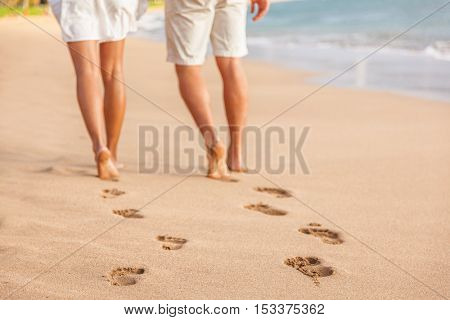 Beach couple relaxing at sunset walking barefoot. Focus on footprints in golden sand. Closeup of legs. Romantic beach vacation holidays. Young people from behind in white shorts and dress beachwear.
