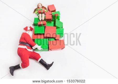 Black Friday 2016 at United States Funny Santa delivering many gift boxes for kids. Little girl sitting at top of big gift box, and holding present. Copy space at white background. Cristmas shopping