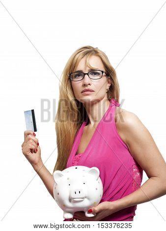 Woman with eyeglasses holding credit card and piggy bank isolated on white