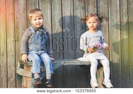 Happy children outdoor at fall season, sitting at bench. First date. Baby boy and girl friendship. Children care. International Children's Day.