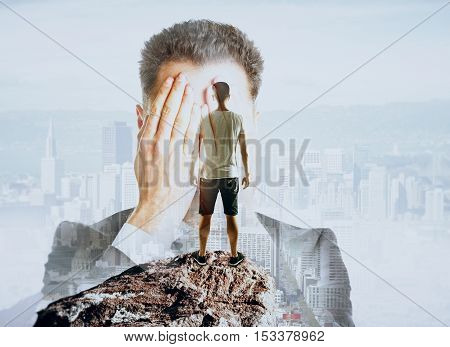 Businessman covering face on abstract background with casual guy standing on mountain top. Fear of failure concept. Double exposure