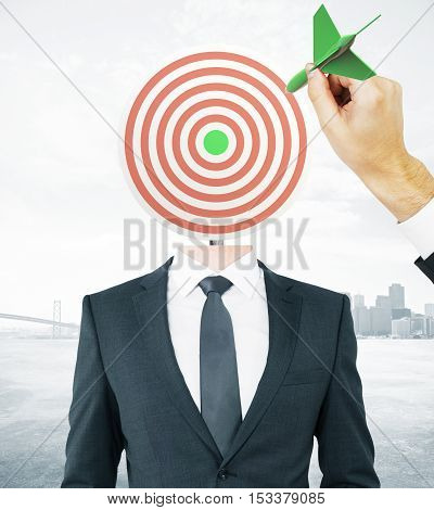 Hand with green dart aiming at target-headed businessman on city background. Aiming and targeting concept