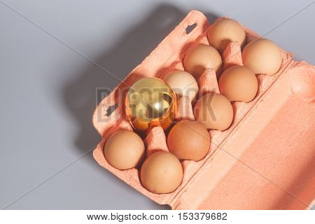 Cardboard egg box with golden and chicken eggs on gray background