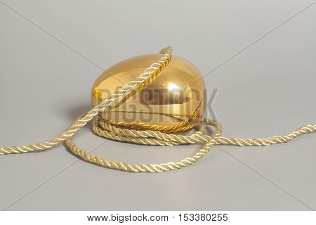 Golden egg with golden rope on gray background