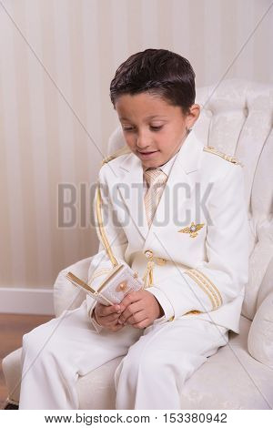 Young boy sitting on an armchair and reading a prayer book in his First Holy Communion.