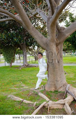 Young boy with white sailor suit leaning on a big tree in his First Communion