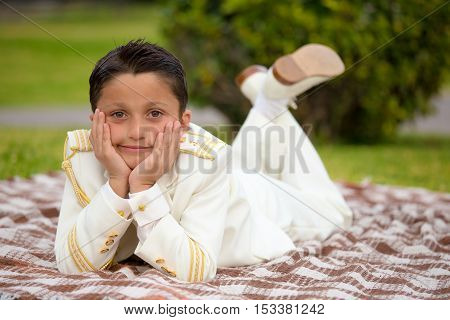Young boy with white sailor suit in his First Communion lying on a blanket over the grass resting his head on his hands and looking at camera. Shallow depth of field.