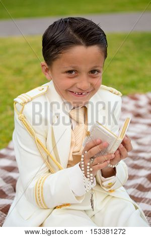 Young boy with white sailor suit in his First Communion smiling with a prayer book and rosary in his hands.