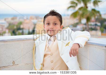 Young boy with white suit leaning on a wall with his elbow in his First Communion.