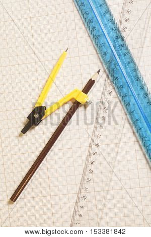 Yellow Drawing compass with black pensil and rulers on graph paper.Engineering concept.