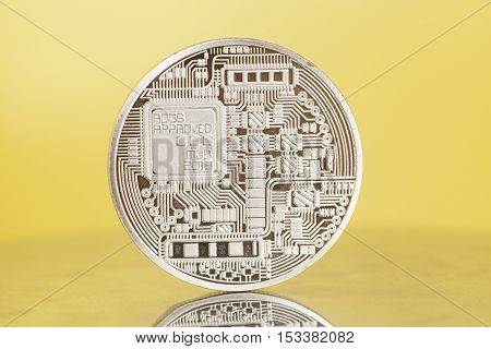 silver bitcoin coin on a yellow background
