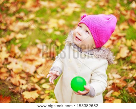 happy baby girl with a ball in the autumn park