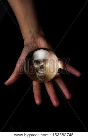 Female hands hold crystal ball with skull for fortune telling background