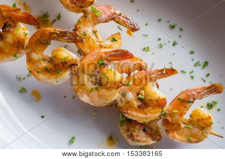 Fresh hot grilled jumbo shrimp kebabs with parsley