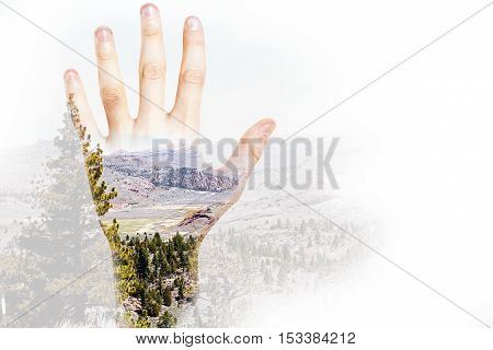 Male hand on abstract landscape background with copy space. Double exposure