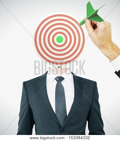Hand with green dart aiming at target-headed businessman on light background. Aiming and targeting concept