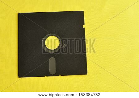 A single floppy disc isolated on yellow background - old technology