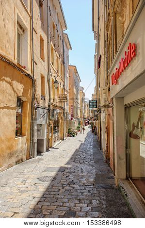 AIX-EN-PROVENCE FRANCE - JUL 17 2014: Romantic tiny street in central Aix-En-Provence South of France on hot summer day with pedestrians and and open cafe and restaurants