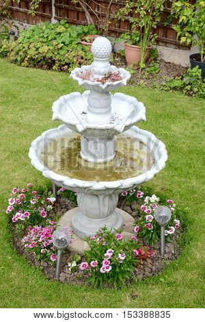 Home garden fountain with freely mowed grass