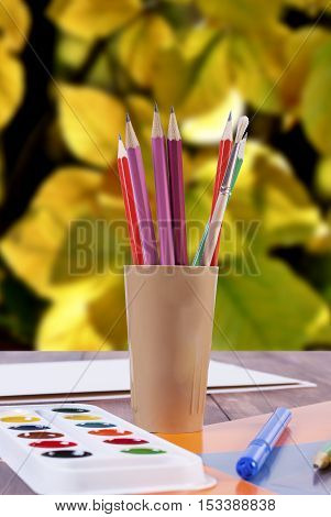 Painting supplies - paint brushes and pencils on the background of autumn leaves