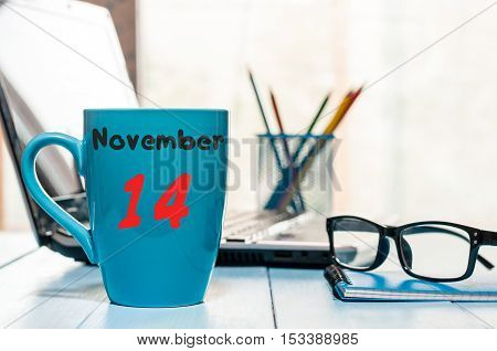 November 14th. Day 14 of month, morning coffee at blue cup with calendar on auditor workplace background. Autumn time. Empty space for text.