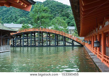 Hiroshima Japan - September 20 2016: Bridge and vermilion halls at itsukushima Shinto Shrine on Miyajima Island. Row of lanterns. Construction barely above sea level.