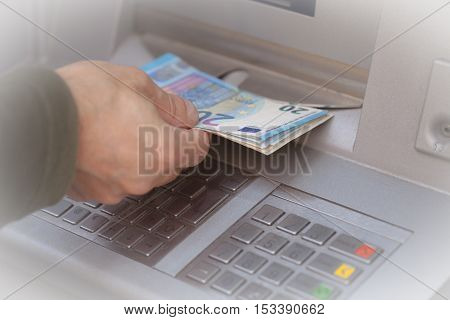 Man hand getting 20 euro banknotes at ATM machine in the bank.