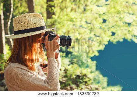 Beautiful young woman photographer taking pictures on the camera outdoors on the nature landscape.