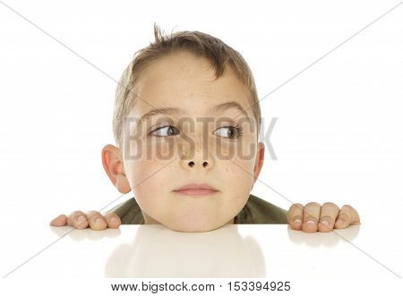 Cute Seven Year Old Boy Peeking Up over a White Table on a White Background