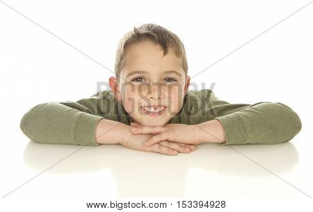 Cute Seven Year Old Boy Peeking Up over a White Table on a White Background resting his head on his arms