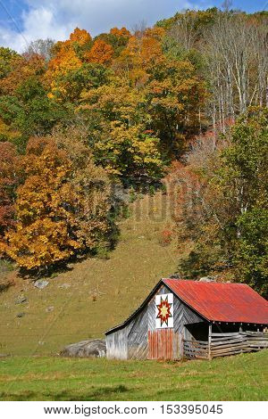 a rustic barn with a red roof and a quilt square, in autumn