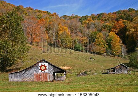 a rustic barn with a quilt square, in autumn
